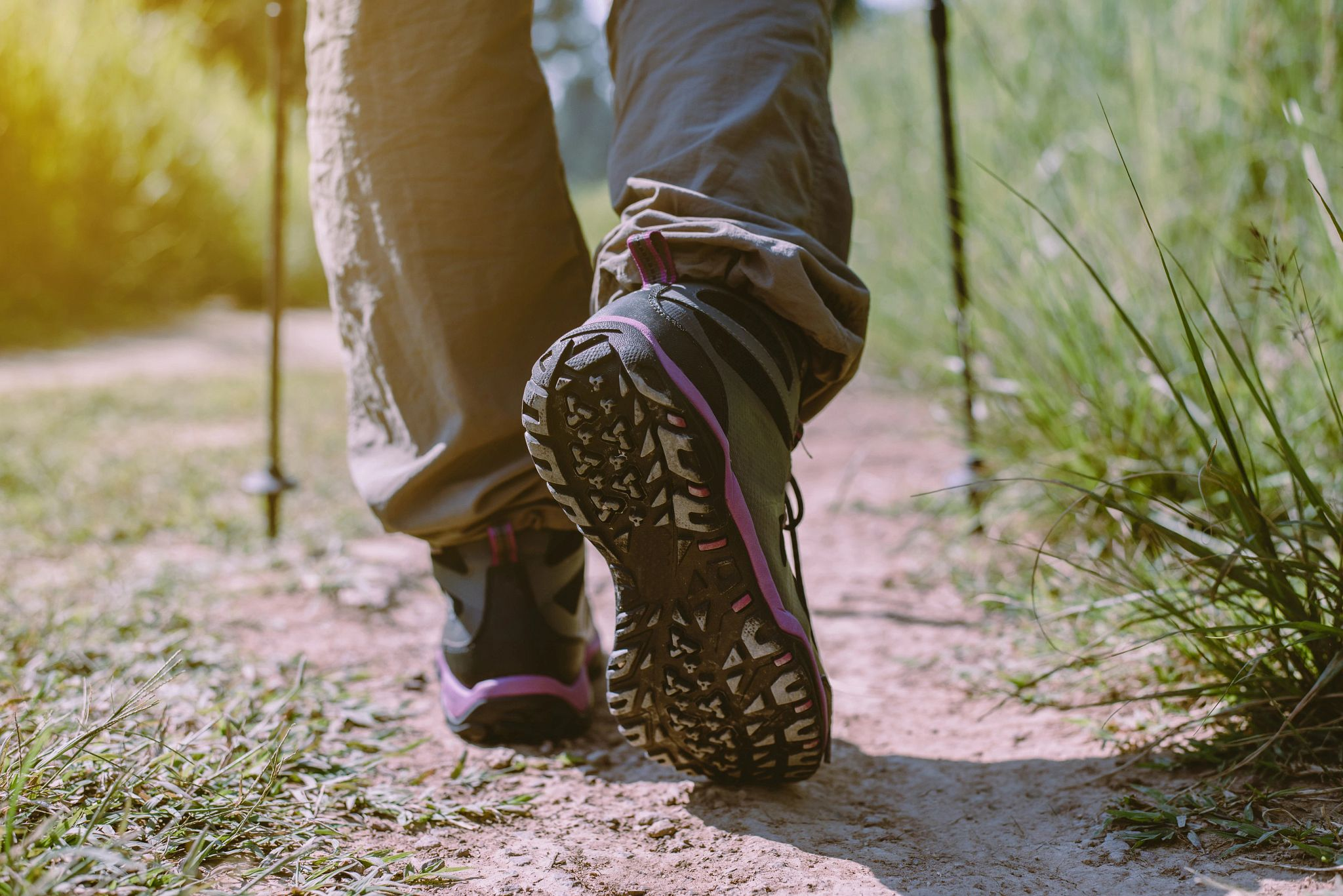 An close-up image of a person's shoes while hiking a trail.