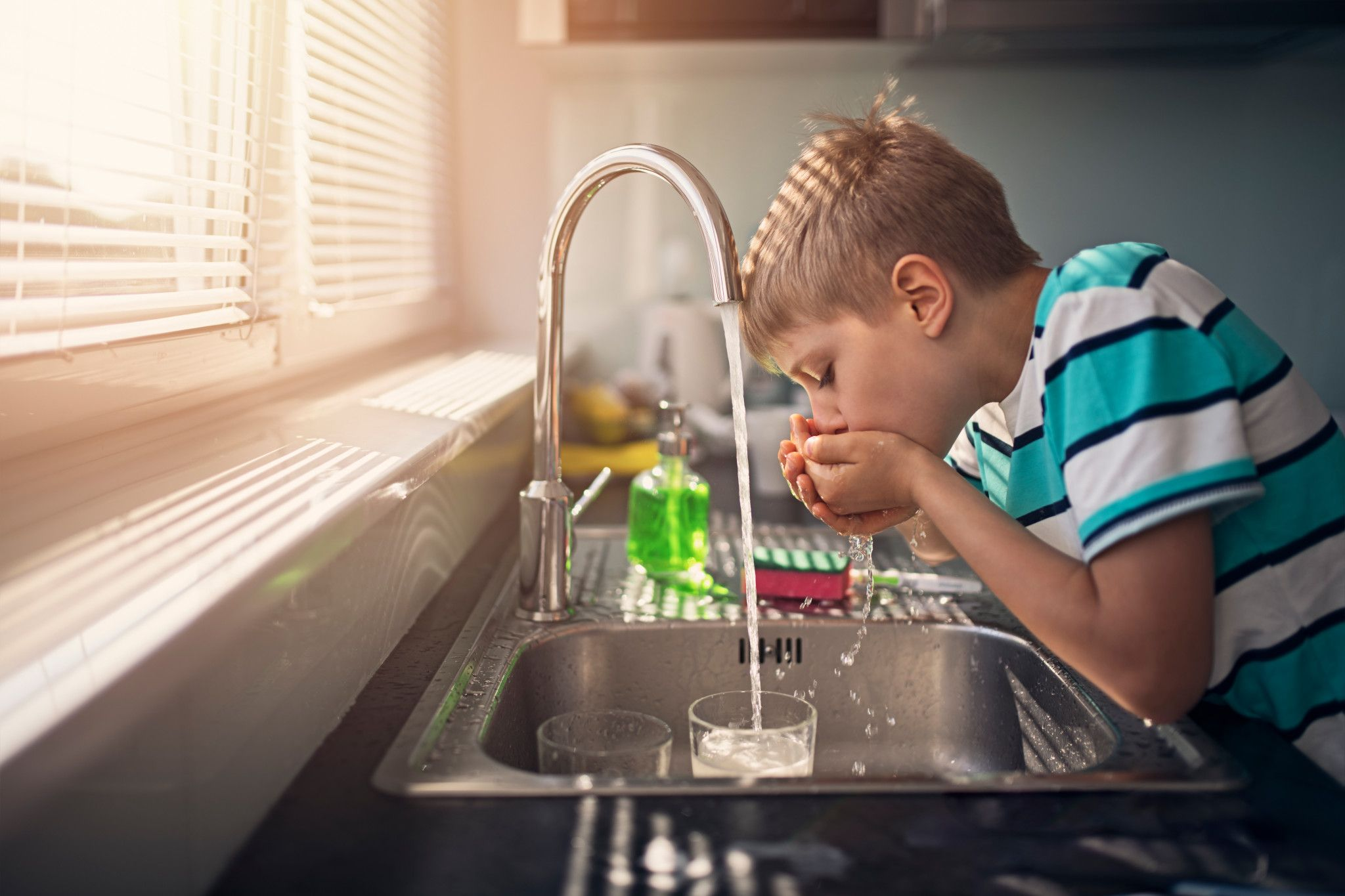 An image of a boy drinking water from the sink.
