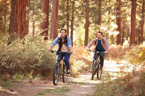 Two men bike side-by-side on a wooded trail.