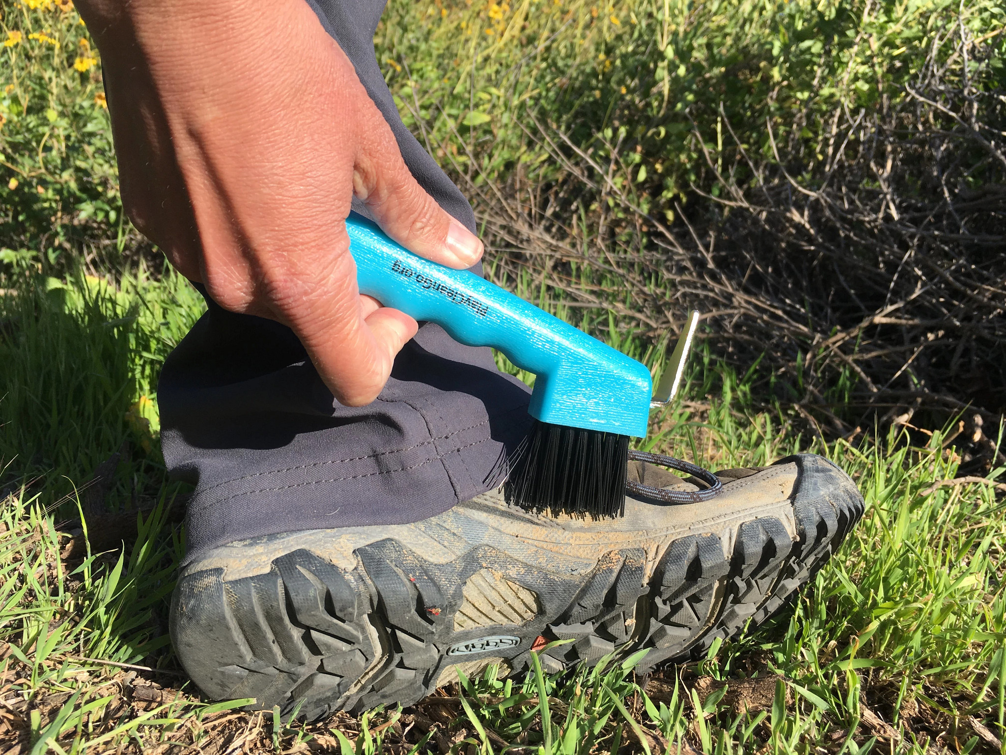 close up of hand scrubbing mud off boot with brush