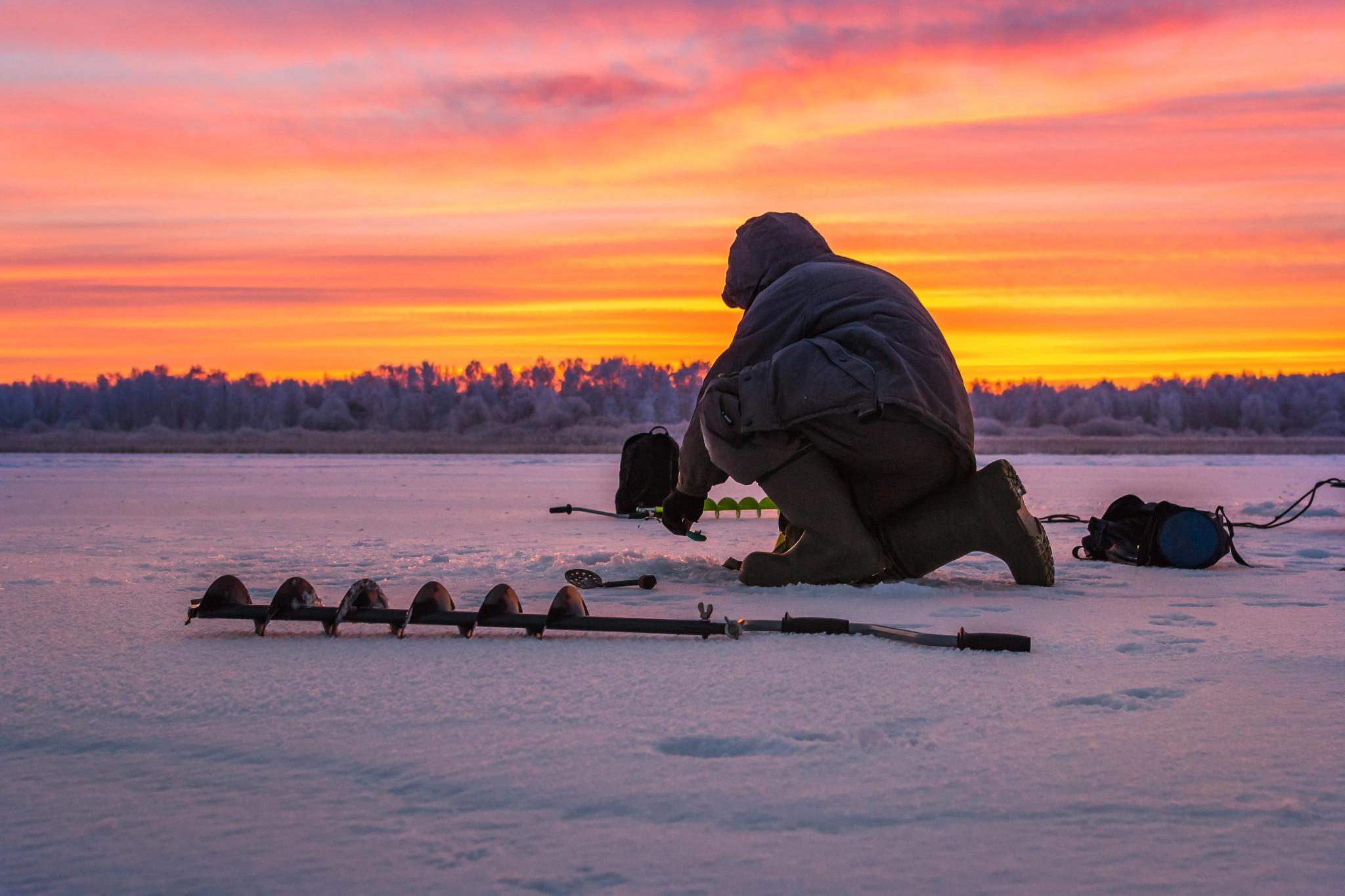 ice fisherman on frozen lake