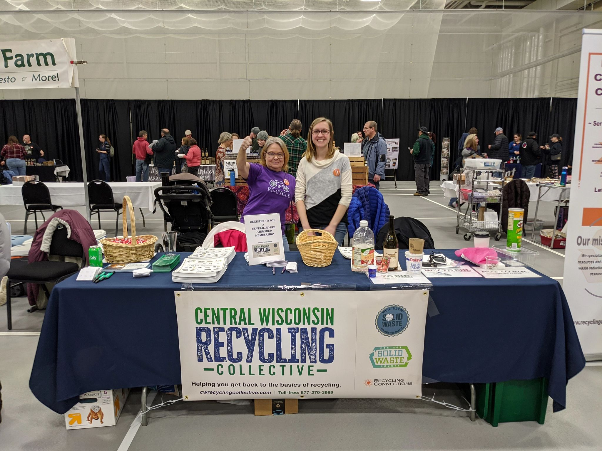 Representatives from the Central Wisconsin Recycling Collective (CWRC) stand in front of their booth.