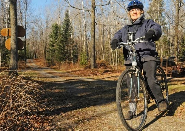 Kay Kavanagh sits on her bike on a wooded path.