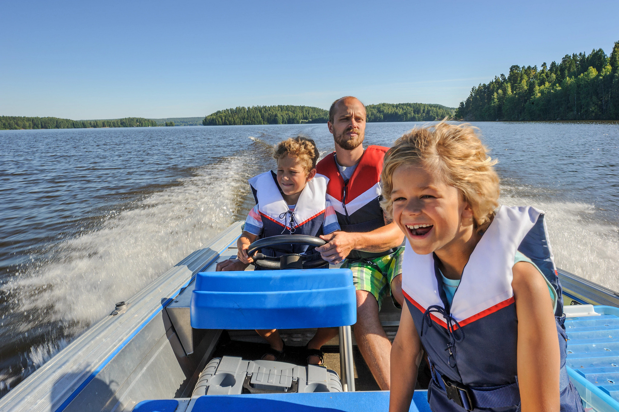 dad and two sons on boat wearing life jackets
