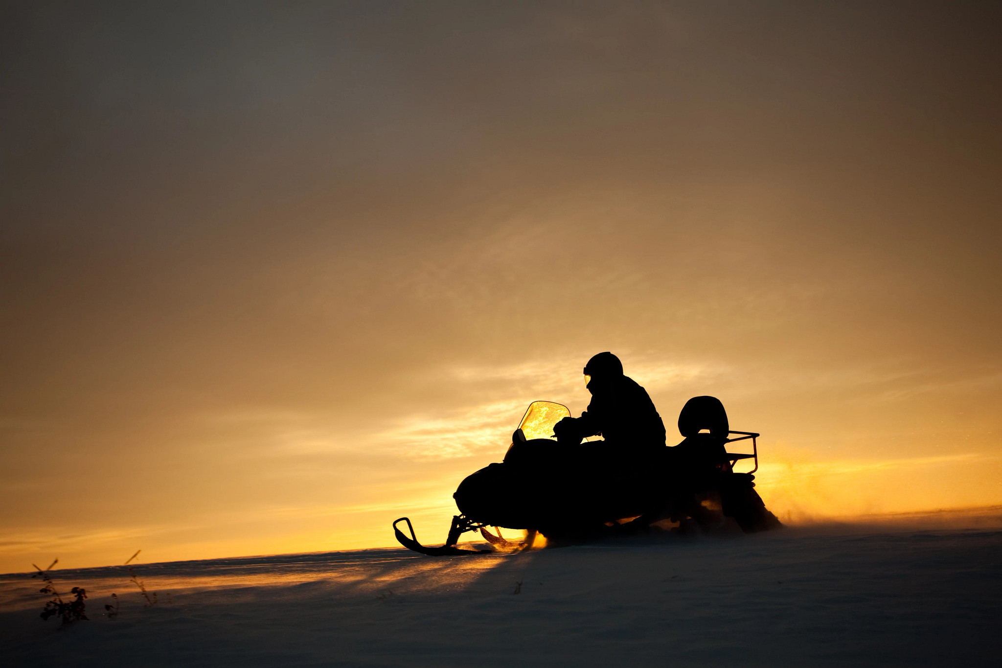A silhouette of a snowmobiler in action.