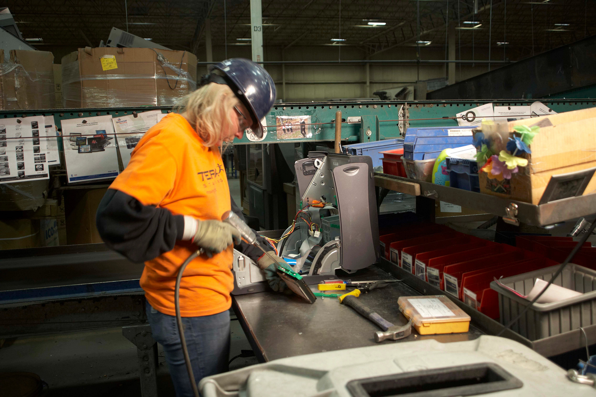 Worker recycles electronics at an E-Cycle collection site.