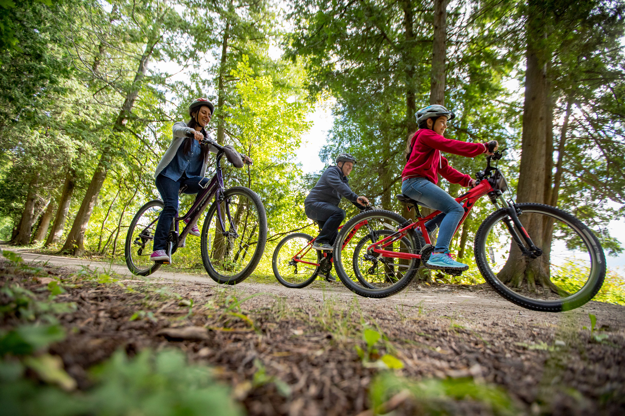 family biking through woods at Peninsula State Park