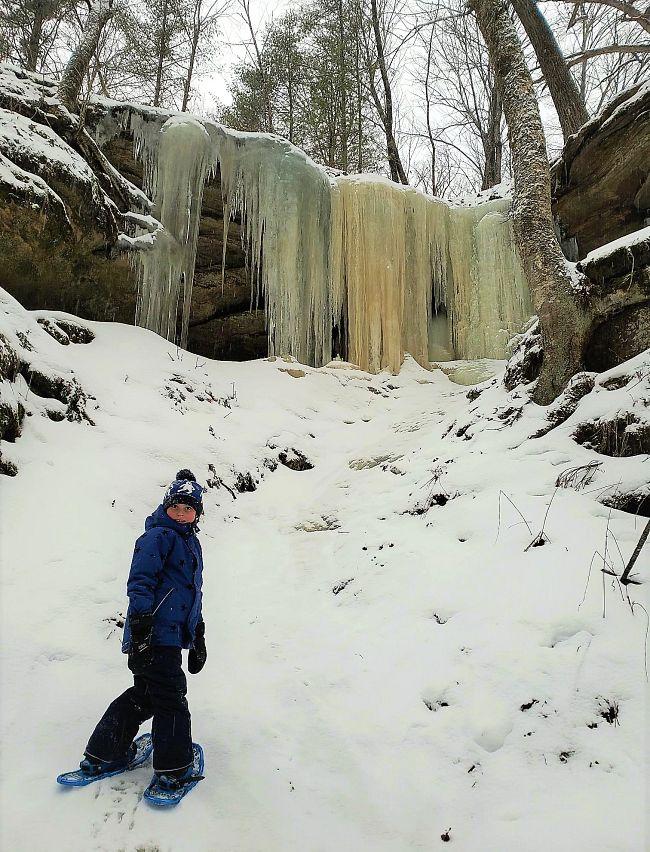 boy snowshoeing by frozen waterfall
