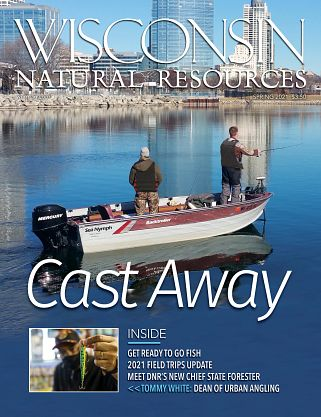 Magazine cover of two men fishing boat with Milwaukee skyline in background