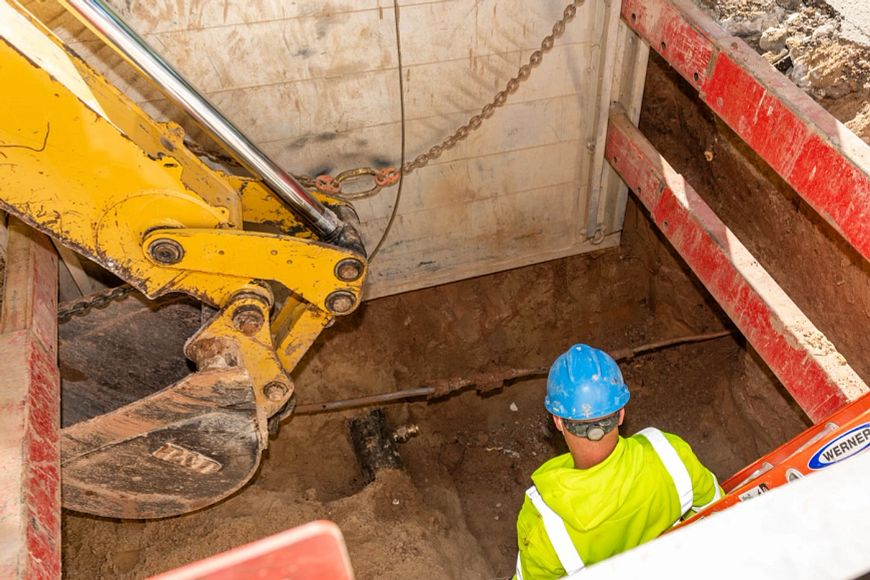 utility worker in a hole where lead service line is being removed