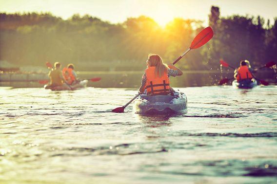 Group kayaking at sunset
