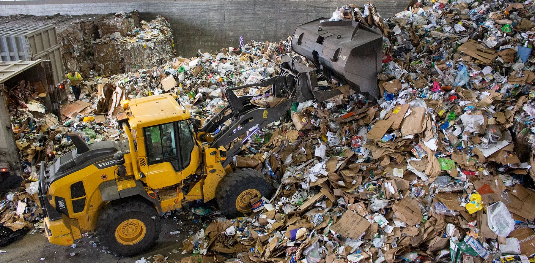 Heavy equipment scoops up a pile of recyclables in a recycling center