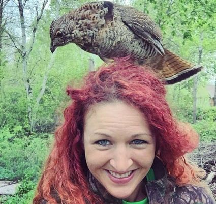 woman with ruffed grouse on her head