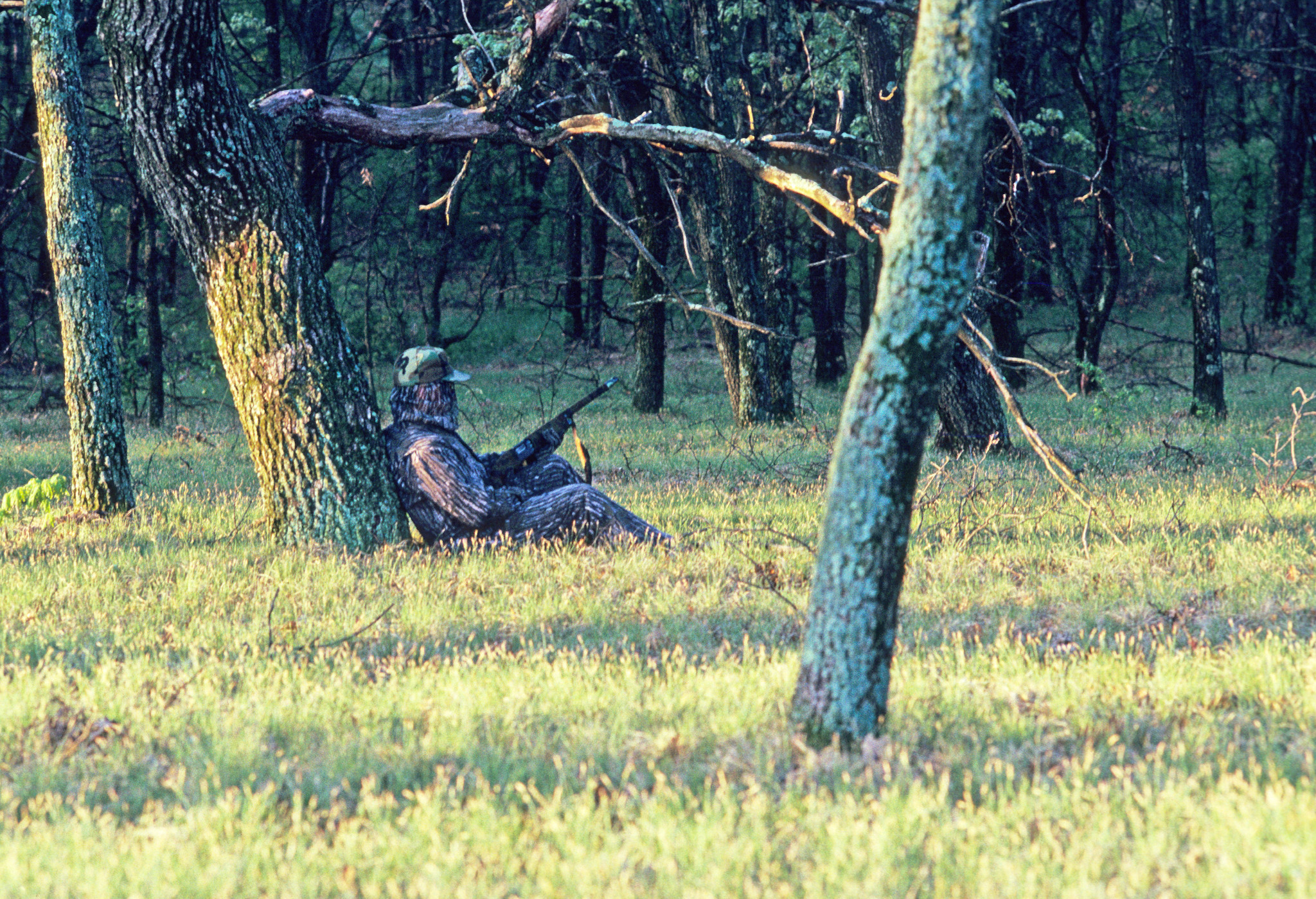 turkey hunter dressed in camo leaning against a tree