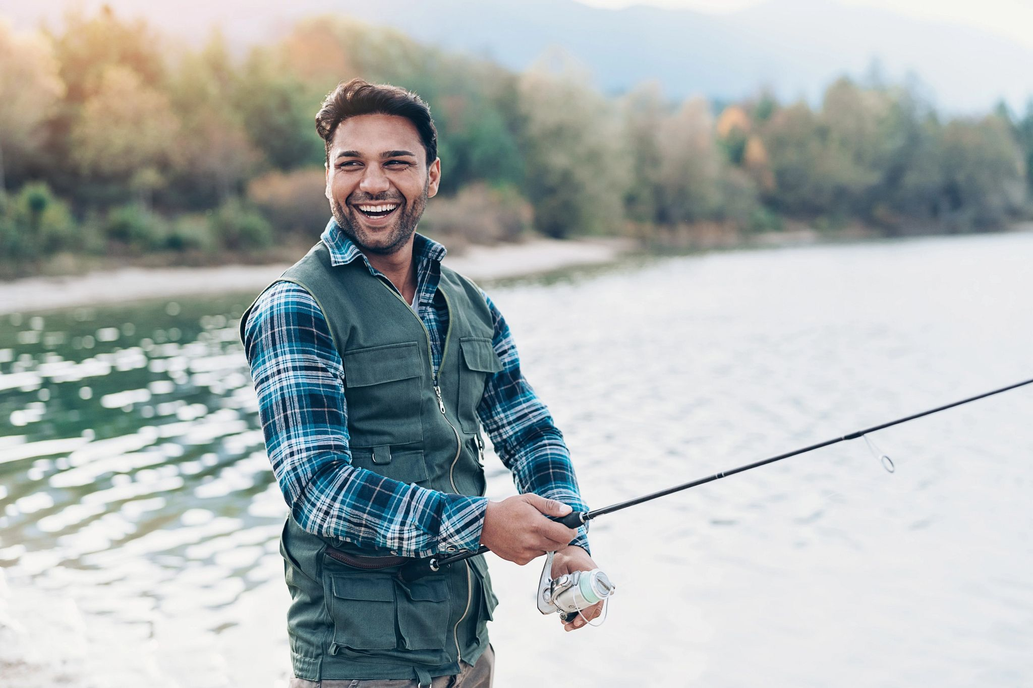 An image of a fisherman smiling while casting his reel.