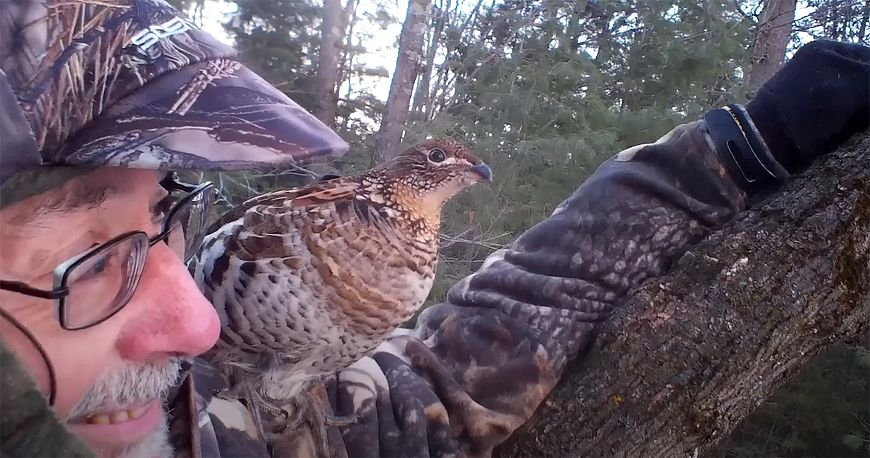 hunter in tree stand with ruffed grouse on his shoulder