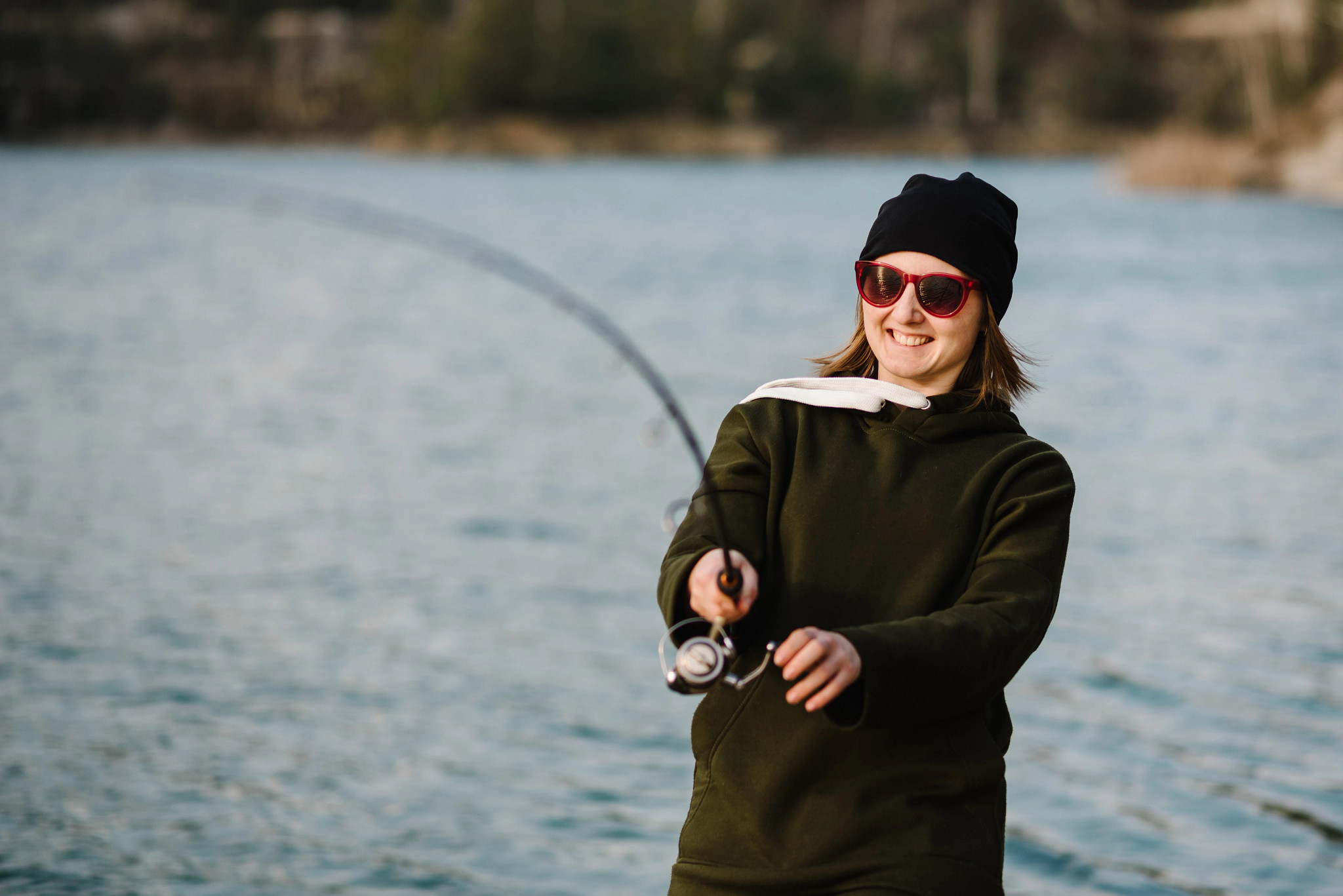 A female angler smiles while holding a fishing rod near a river.