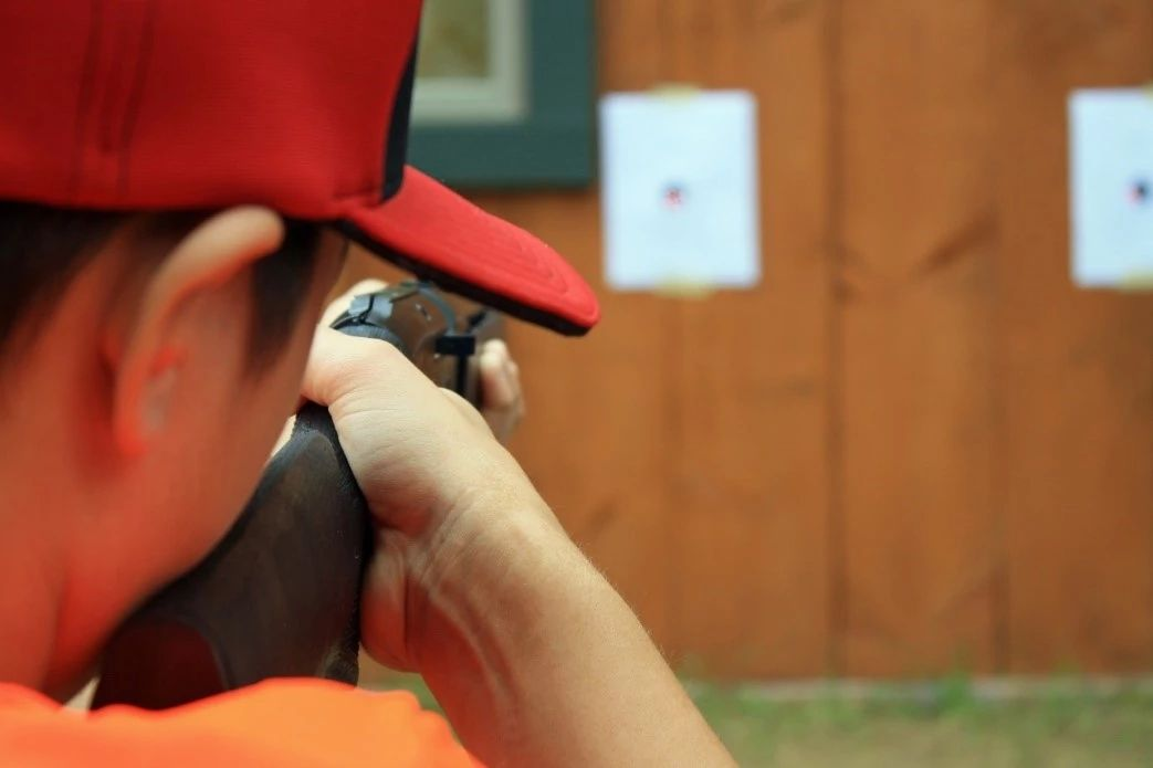 An image of a hunter looking through the rear-sight post of their rifle.