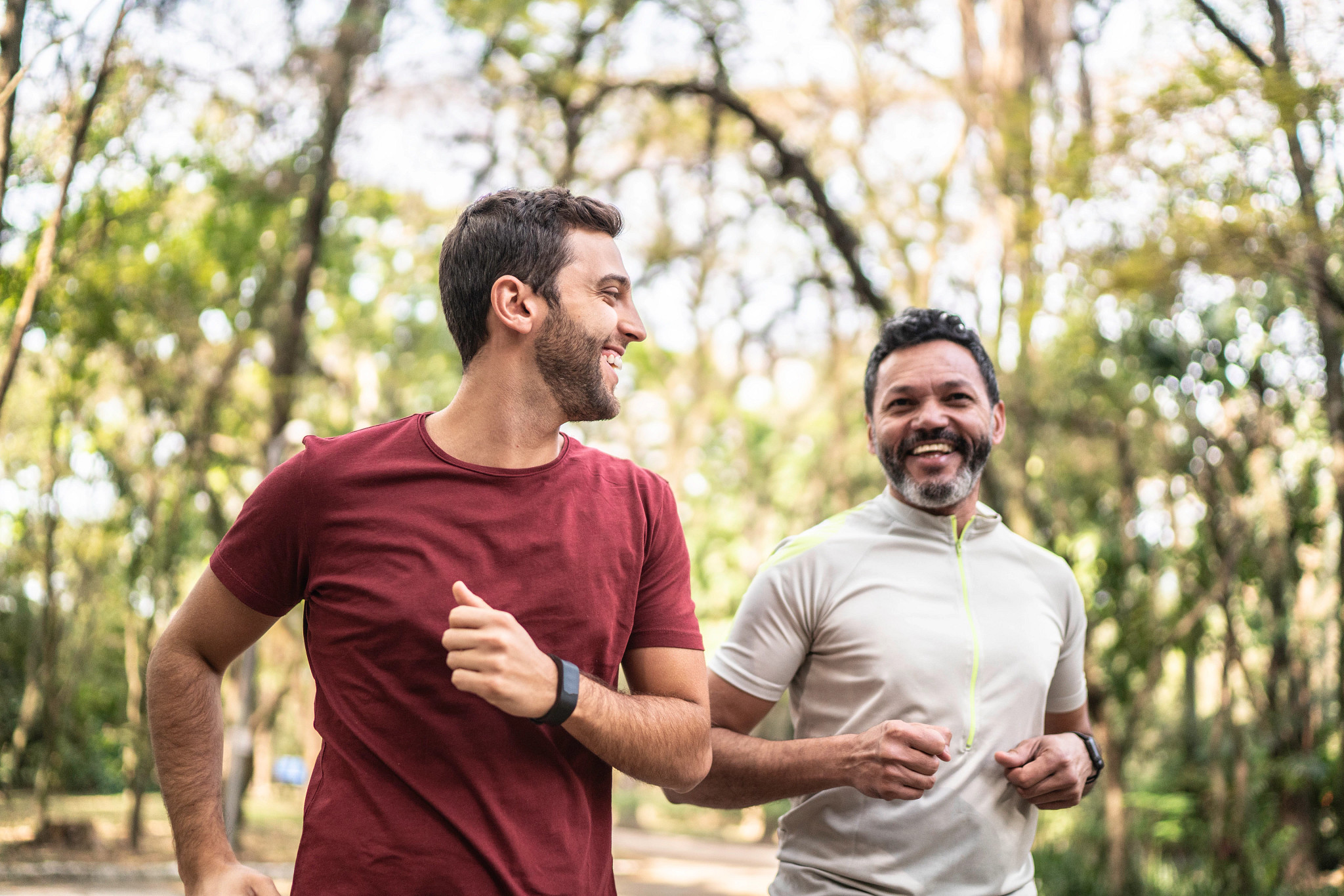 two male friends running together through a shady park