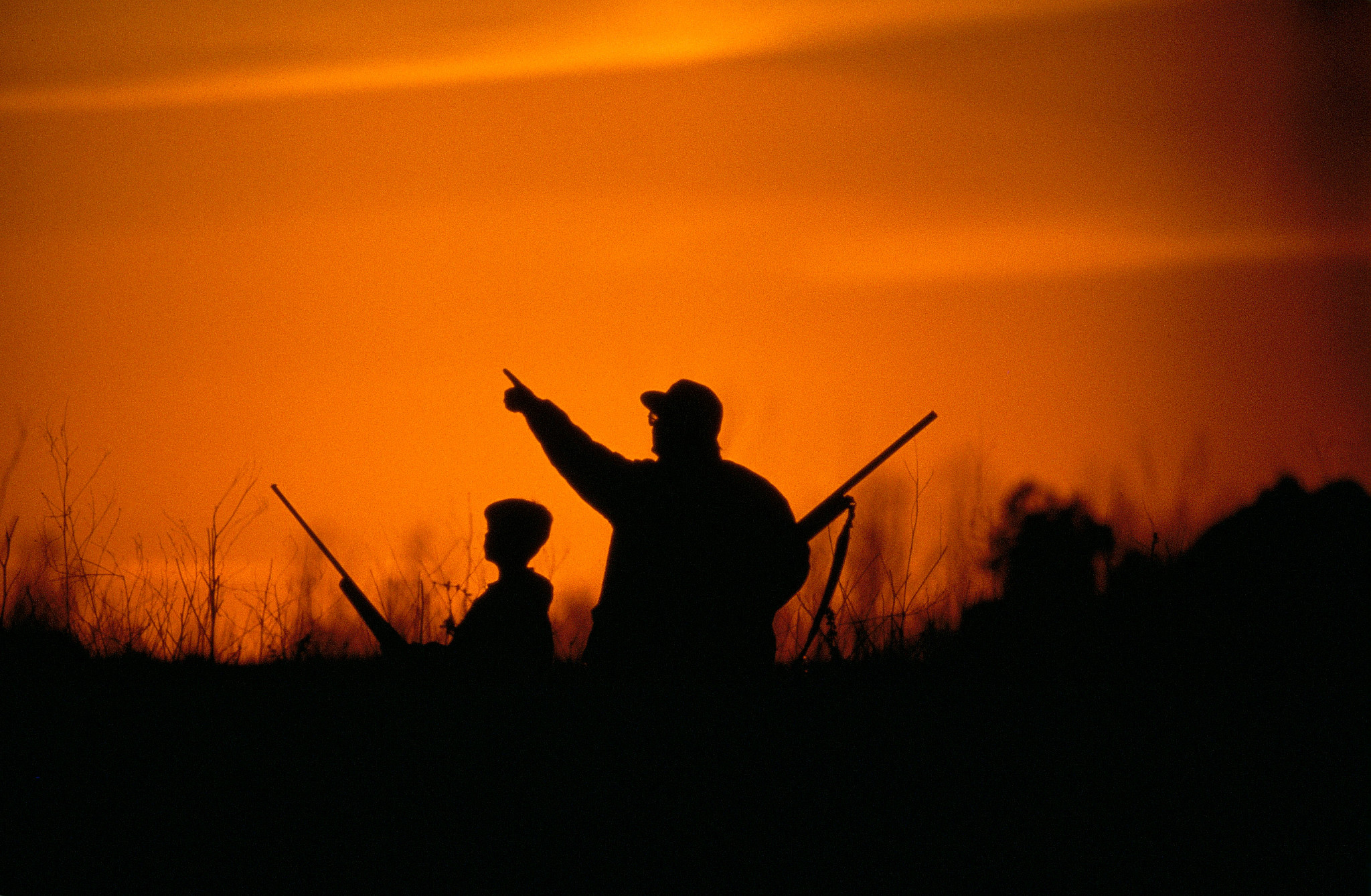 father and son waterfowl hunting during sunset