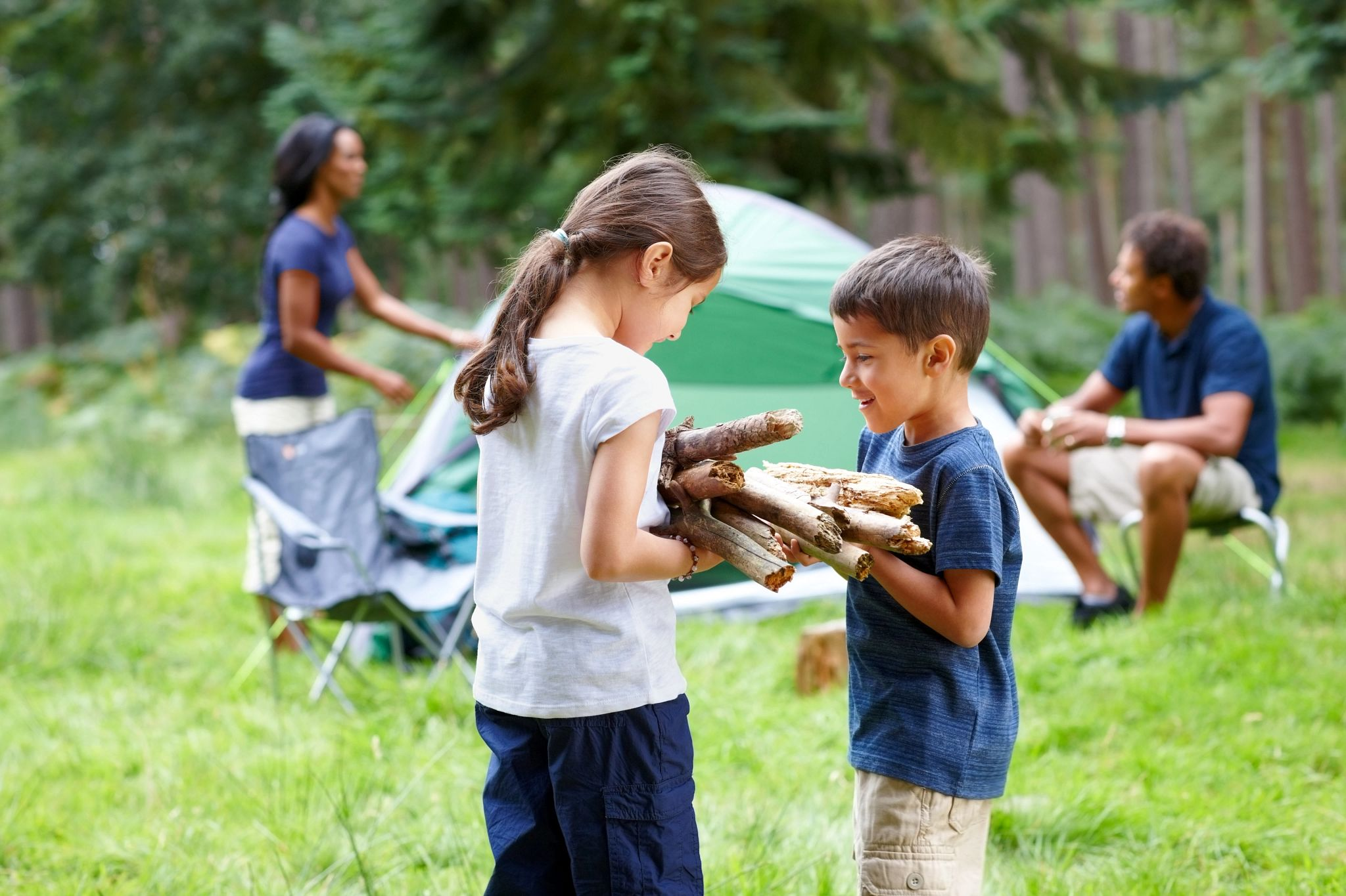 An image of a child handing firewood to another child.