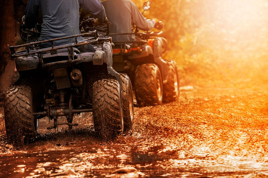 Two people riding ATVs on off-road trail