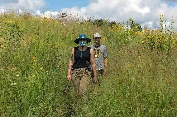 two people in masks walking in prairie
