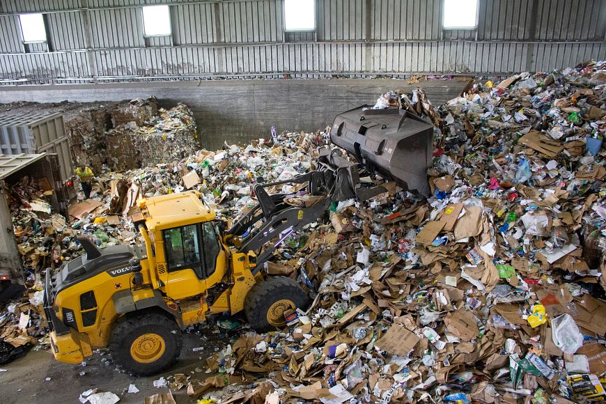a front loader pushes recyclables