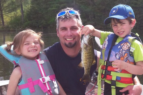 man and his two children holding caught fish