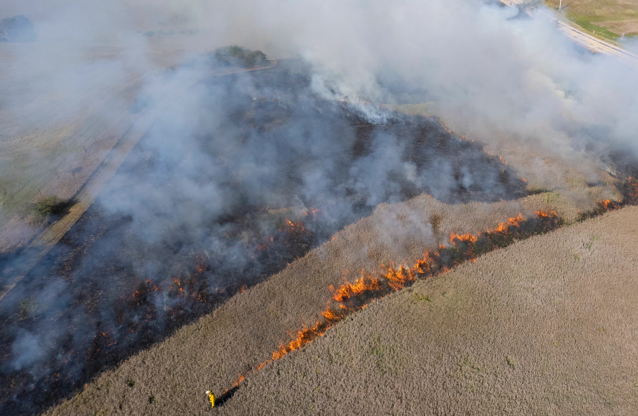 A DNR burn crew member walks along open conservation area conducting a controlled burn of sections