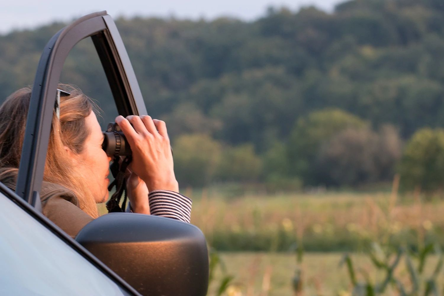 An image of a woman looking through binoculars while sitting in a vehicle.