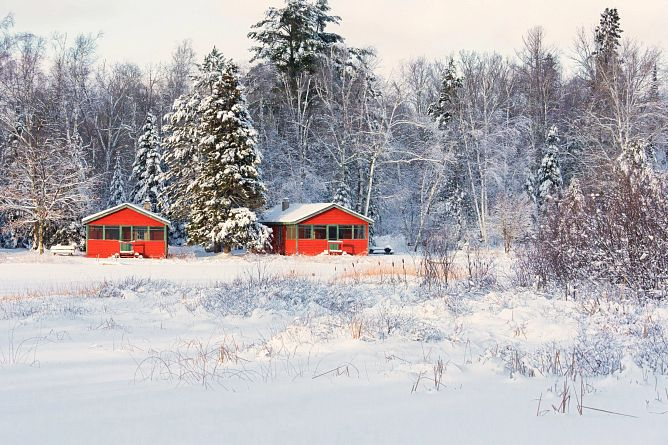 two bright red cabins on a snowy landscape