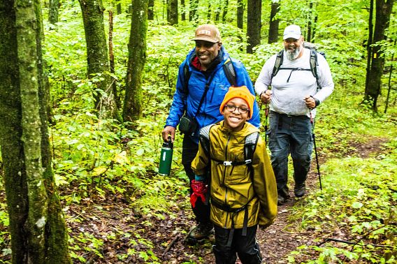 smiling boy and two adults hiking in woods