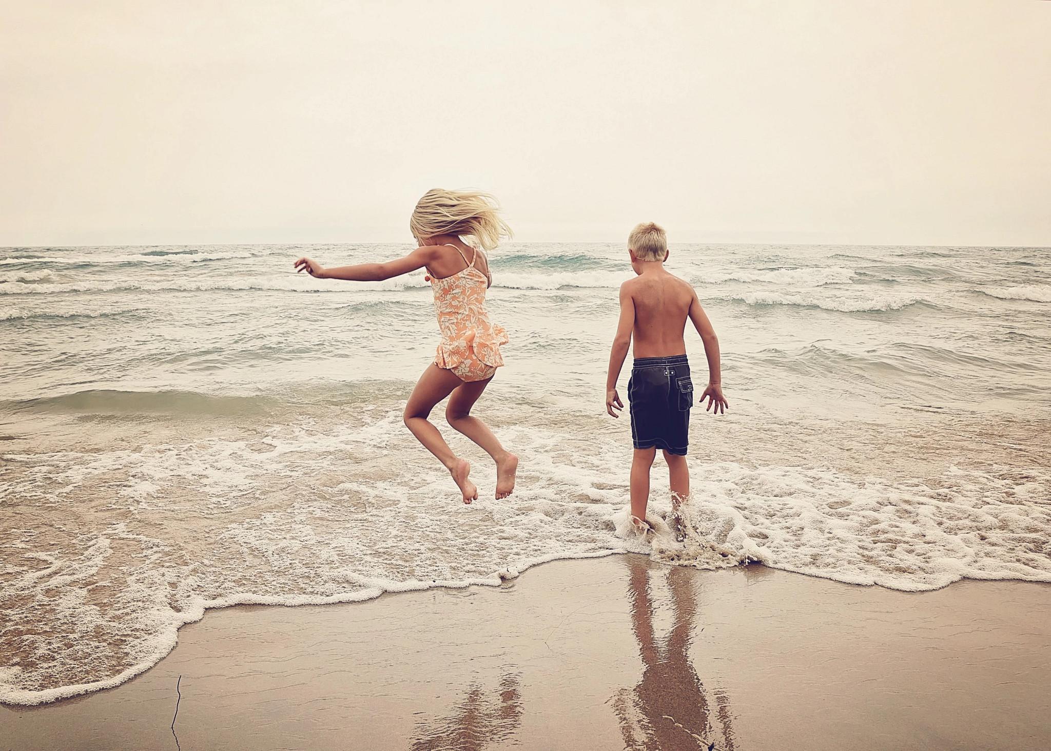 little boy and little girl splashing in waves on sandy beach