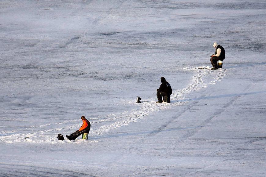 three anglers on frozen ice