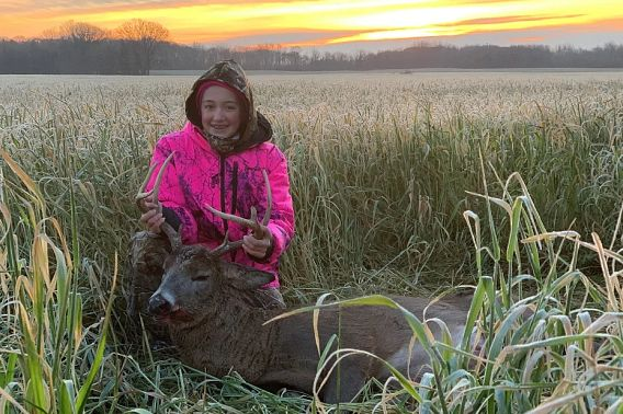 young girl at sunrise with first harvested buck
