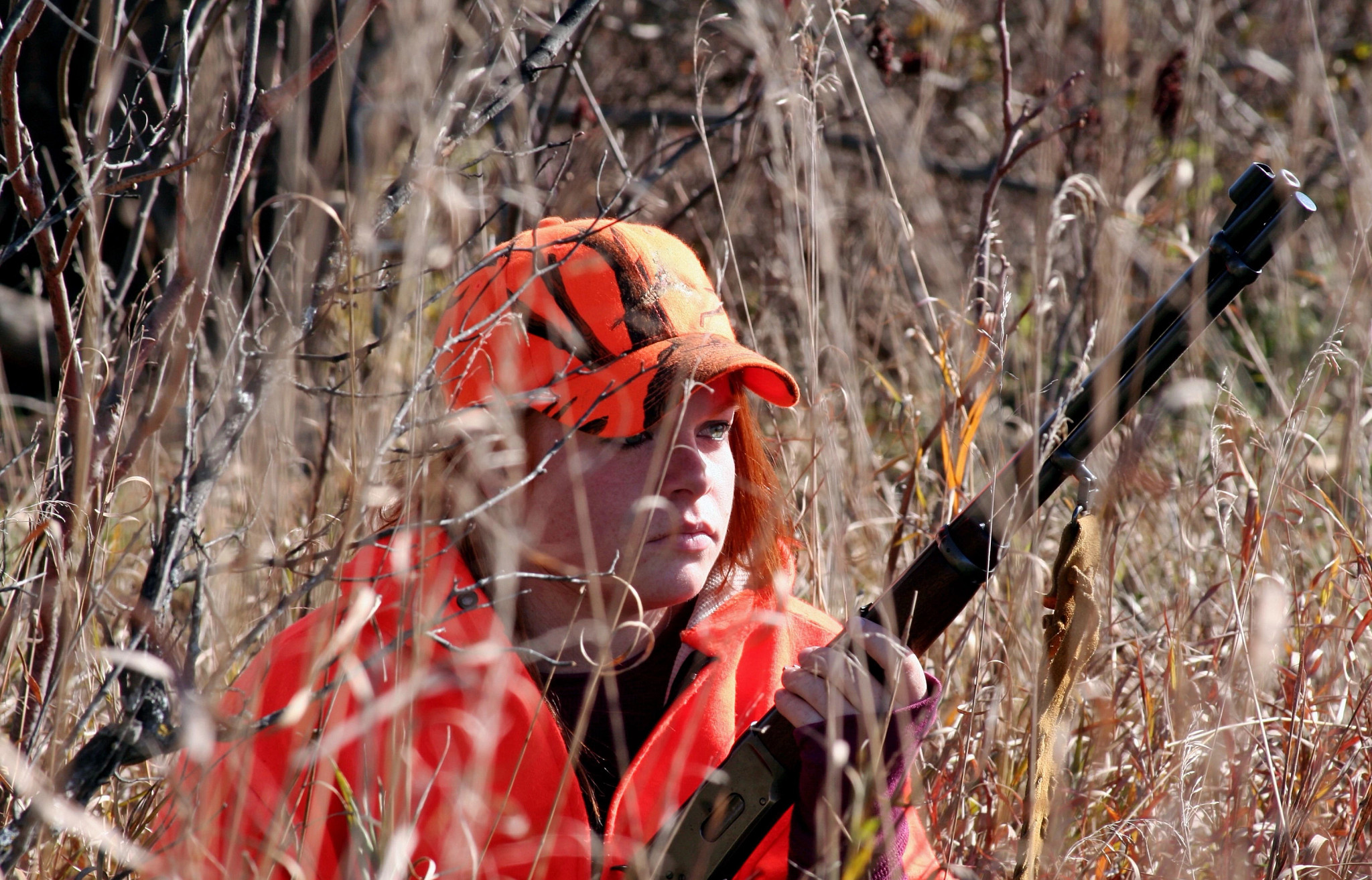 A woman hunting in a field.
