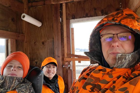 man in hunting blind with two grandkids