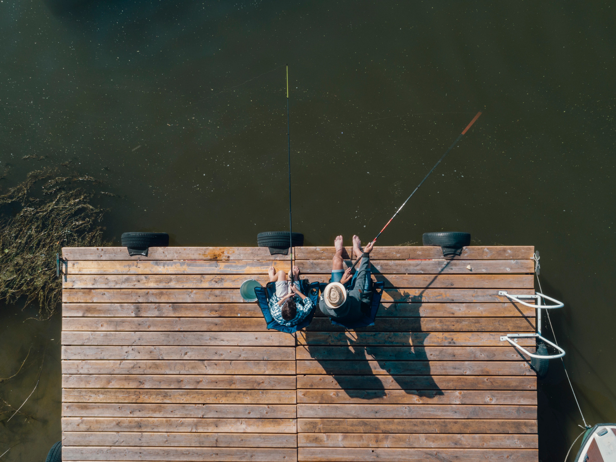 aerial photo of a man and boy fishing off a dock
